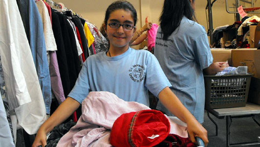 young girl volunteer with basket full of clothes