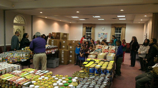 volunteers gathered around open square of tables full of food